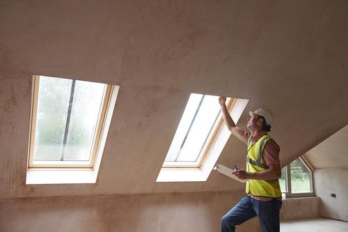 Bauinspektor kontrolliert die Fenster.